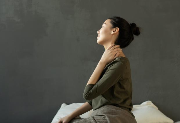 Девушка в зеленой блузе держится за шею