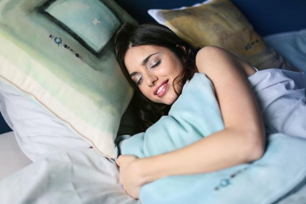 девушка обнимает подушку и улыбается