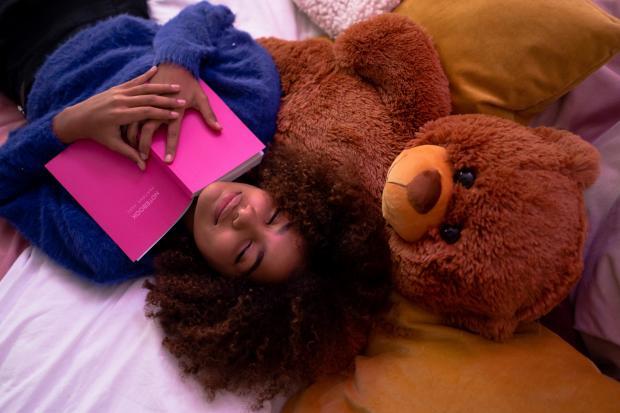 девушка держит книгу и улыбается с закрытыми глазами