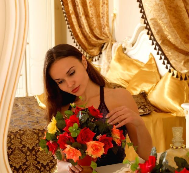 красивая девушка рассматривает букет цветов