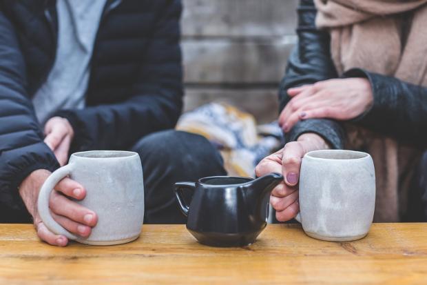 двое пьют чай из белых кружек и черного чайника