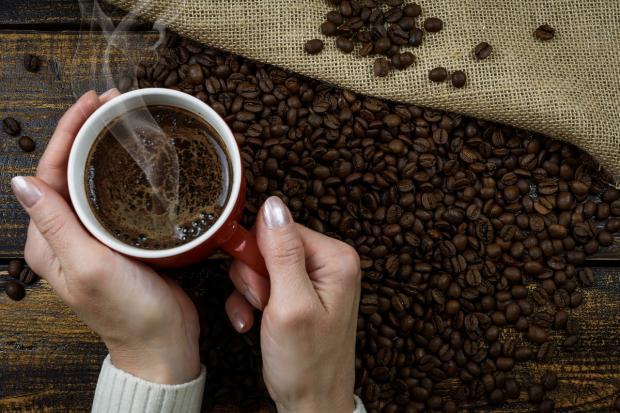 девушка держит кружку кофе в ладонях