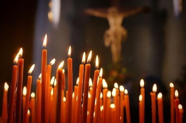 горящие перед крестом с Иисусом Христом церковные свечи
