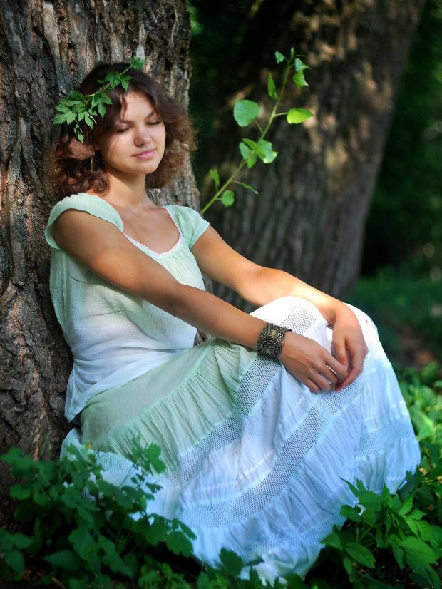 красивая девушка сидит под деревом