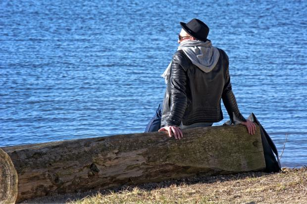 молодой человек сидит на берегу моря