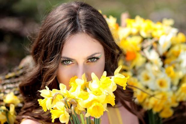 девушка спряталсь за букетом желтых цветов