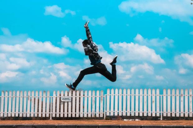 человек перепрыгивает через забор