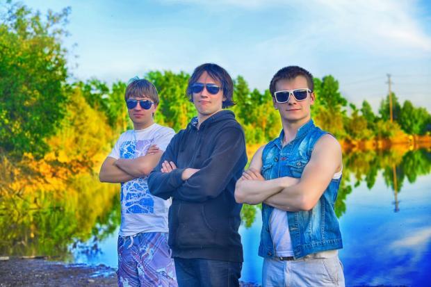 молодые мужчны стоят на берегу реки