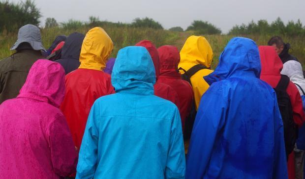 люди стоят в разноцветных дождевиках