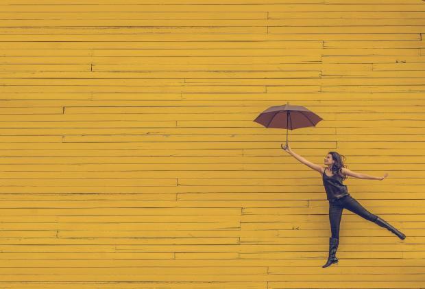 Женщина с зонтом на желтом фоне