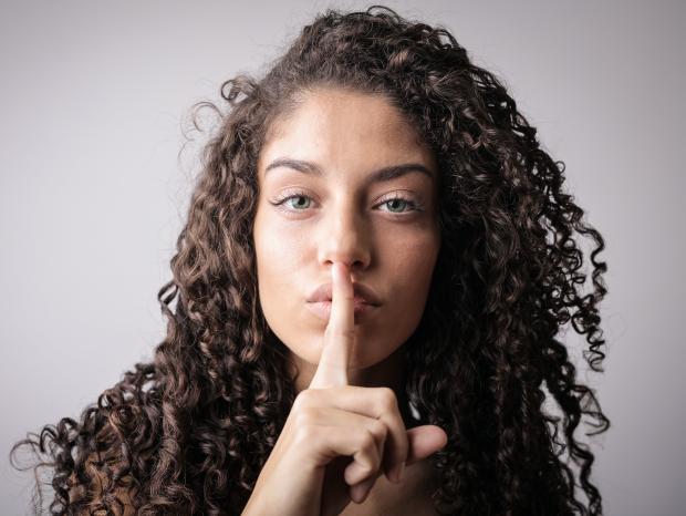 кудрявая девушка приставила палец у рта