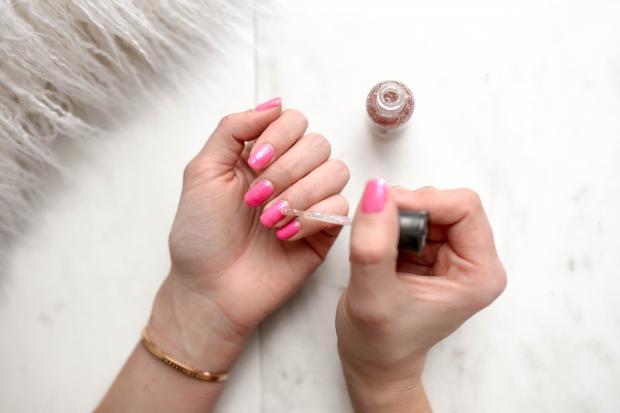 Женщина наносит лак на ногти