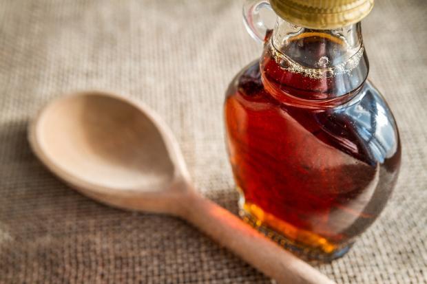 Кленовый сироп в бутылке и деревянная ложка