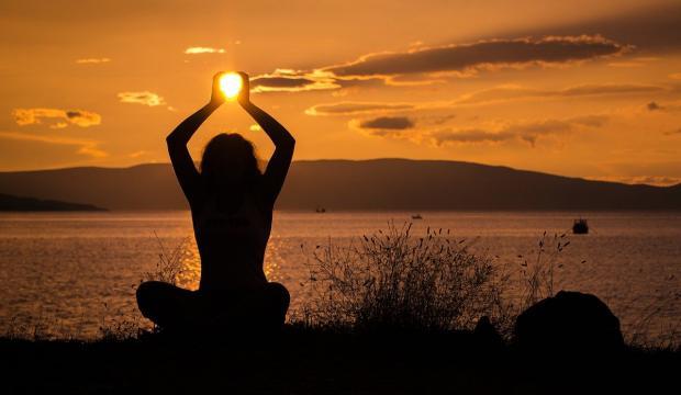 медитация на берегу моря при закате солнца