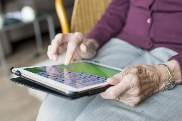 пожилая женщина играет на планшете
