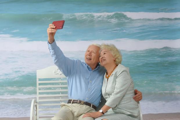 пожилая пара на берегу моря сиит на скамейке