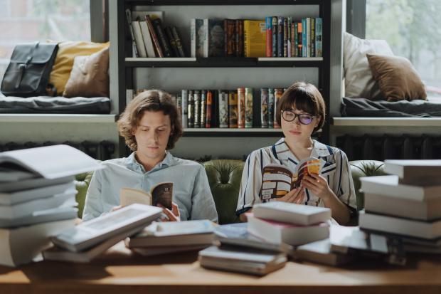 молодой человек и девушка читают книги