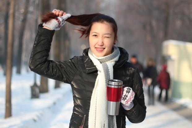 девушка с чашкой тянет себя за волосы