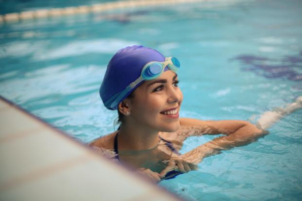 девушка в бассейне в резиновой шапочке