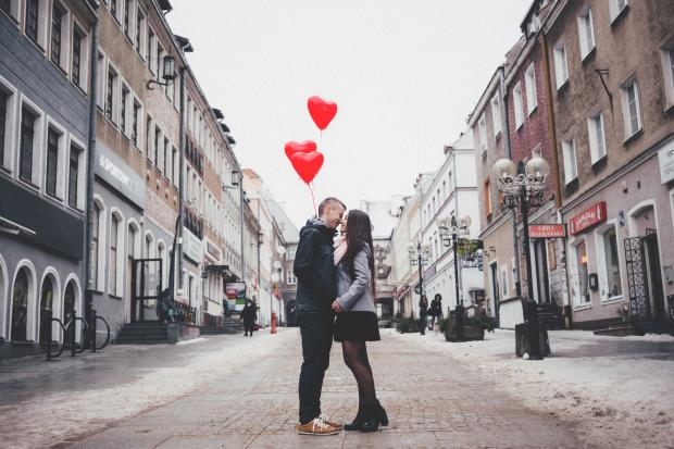 целующаяся пара молодых людей держит в руках воздушные шарами