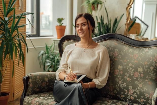 женщина с блокнотом сидит на диванчике