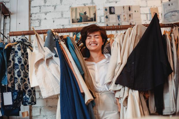 девушка в магазине одежды с нарядами в руках