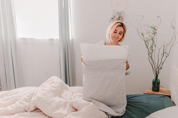 девушка заправляет наволочку в подушку