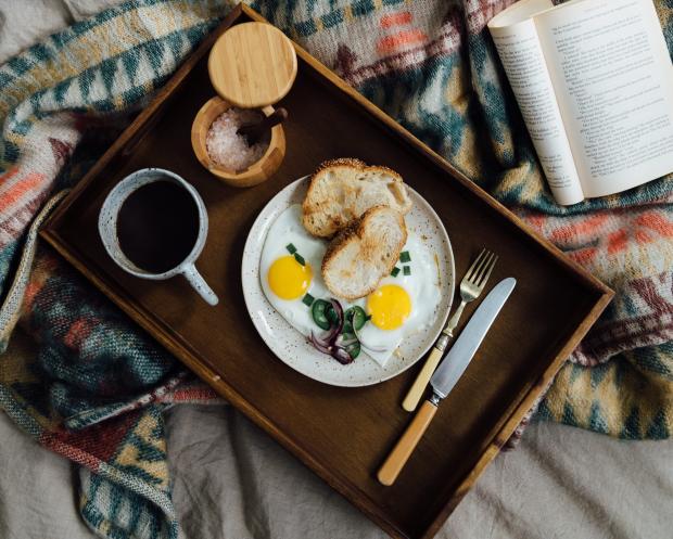 тарелка с яичницей и чашка с кофе на деревянном подносе