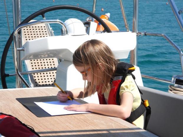 девочка делает уроки на лодке