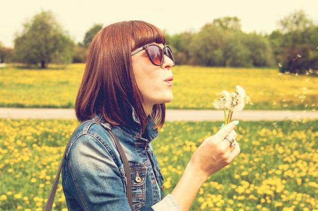 девушка в солнцезащитных очках дует на одуванчик