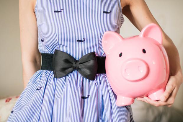 Девушка в голубом платье держит розовую копилку