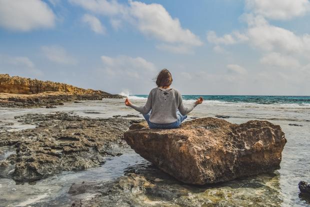 девушка медитирует на камне на берегу моря