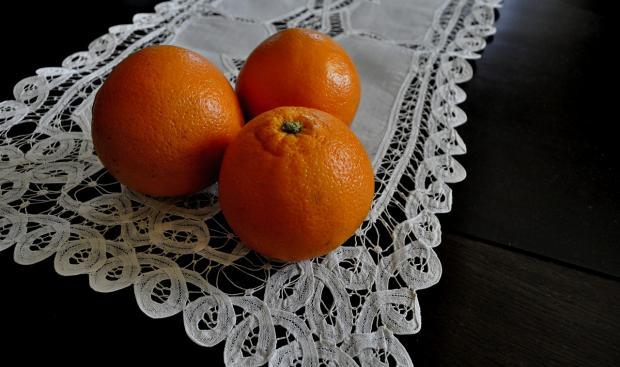 три апельсина лежат на белой кружевной салфетке