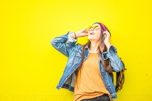 Девушка в желтой футболке красных наушниках и джинсовой куртке стоит возле желтой стены