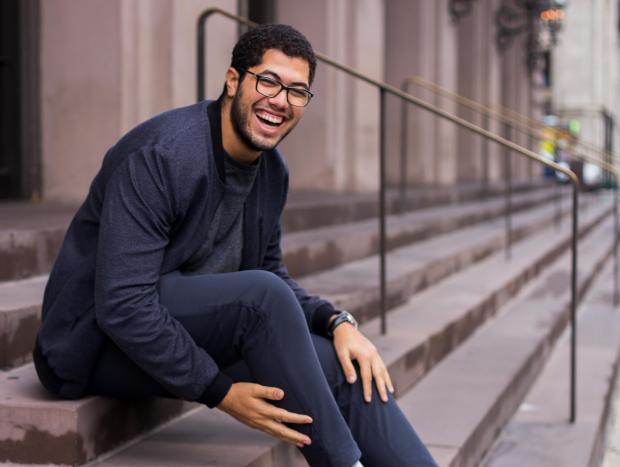 Молодой мужчина в темной одежде сидит на лестнице