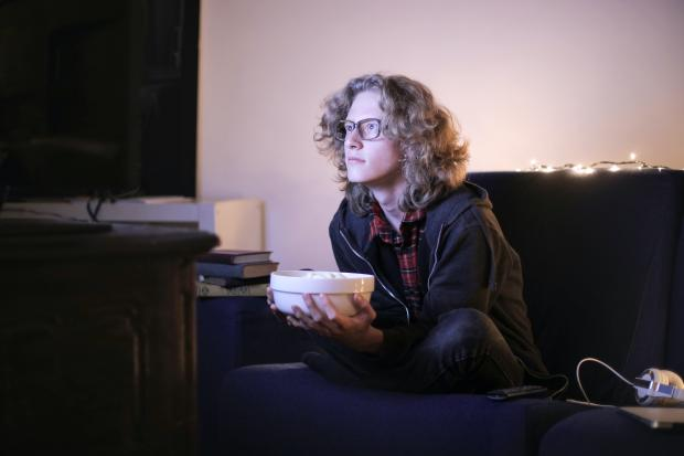 Молодой мужчина смотрит телевизор