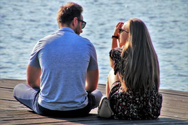 парень и девушка сидят у воды и разговаривают