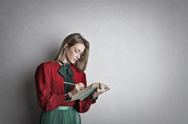 Девушка в красной блузе и зеленой юбке с книгой в руках