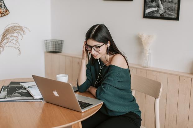 девушка в зеленом свитере перед компьютером