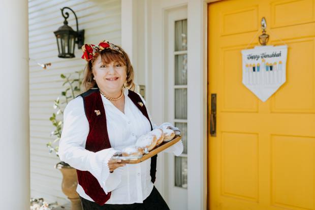 женщина с подносом пончиков у желтой входной двери