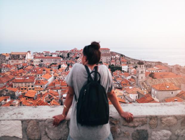Девушка с рюкзаком на фоне Дубровника