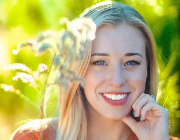 улыбающаяся светловолосая девушка на природе