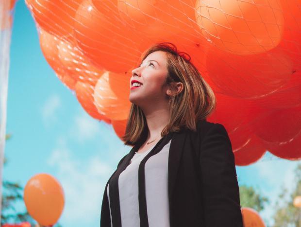 молодая девушка в костюме на фоне воздушных шаров