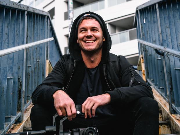 молодой мужчина в черном худи сидит на лестнице