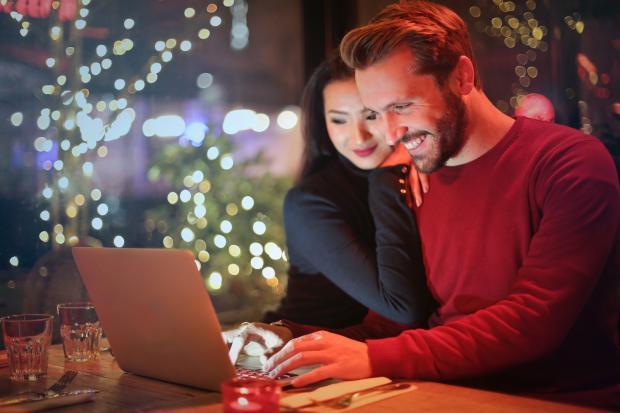 девушка прижимается к мужчине, работающему на ноутбуке