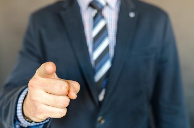 мужчина в костюме показывает пальцем