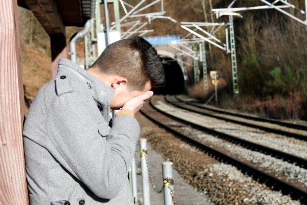 мужчина плачет рядом с железной дорогой
