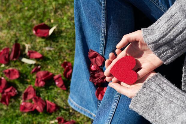 девушка держит в руках фигурку сердца