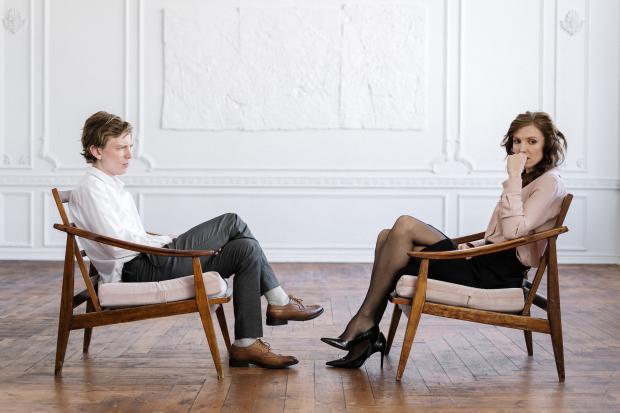 мужчина и женщина сидят на стульях напротив друг друга