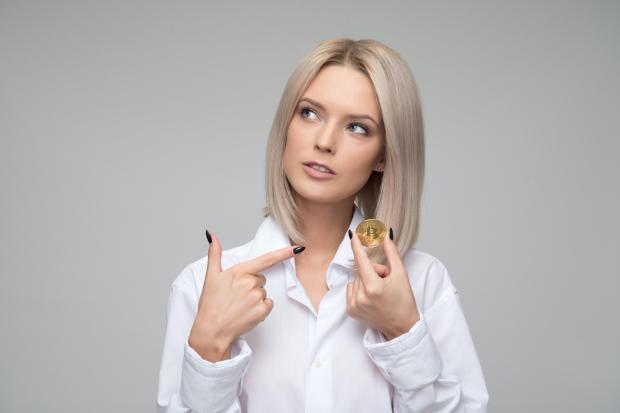 девушка-блондинка держит в руке монетку